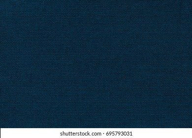 Dark navy blue background from a textile material with wicker pattern, closeup. Structure of the denim fabric with natural texture. Cloth backdrop.