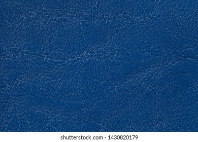 Dark navy blue leather texture background, closeup. Denim cracked backdrop from wrinkle skin, structure of textile.