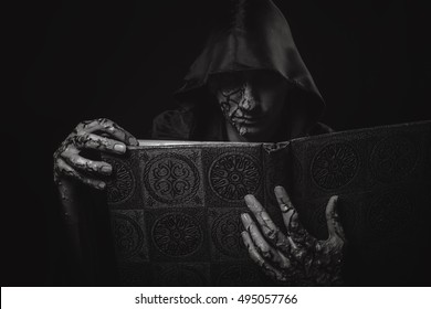 Dark necromancer and grimoir, a warlock casting black magic from his magic book, halloween concept, black and white