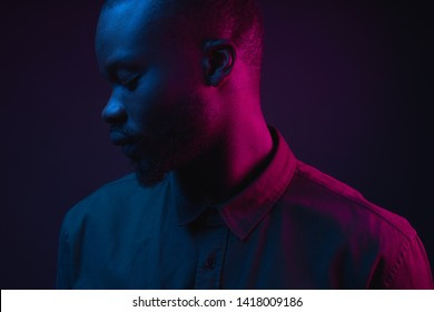Dark neon portrait of young man with beard, wearer in shirt. Pink and blue light. Technology