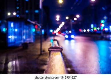 Dark night in the big city, the bus stop and the headlights of the approaching car. Defocused image, image in the blue tones