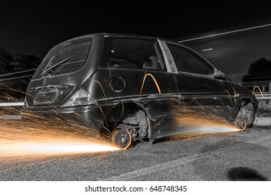 In the dark of the night a black car with sparks coming out of the wheels