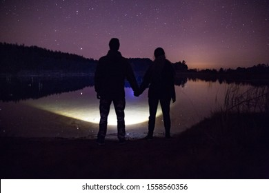 Dark night with a bright sky full of stars near the huge lake and the forest in the distance. Two black figures standing together holding hands and looking into the distance