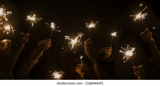dark night celebrate concept with lot of hands taking and using light sparkles fire together. have fun for new year eve or party. companionship and friendship during celebration. happy lifestyle