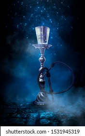 Dark night magic scene. Eastern hookah with smoke on the old cobblestone road. Blue neon, moonlight at night.