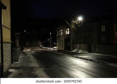 Dark night, road between old wooden houses. Tallin, Estonia. Lanterns in abandoned mistic town