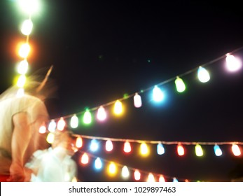 dark night sky background with out of focus blur colourful festive lighting party style lantern lamp hanging outdoor and motion blur moving dancing human figures for fun events backdrop background