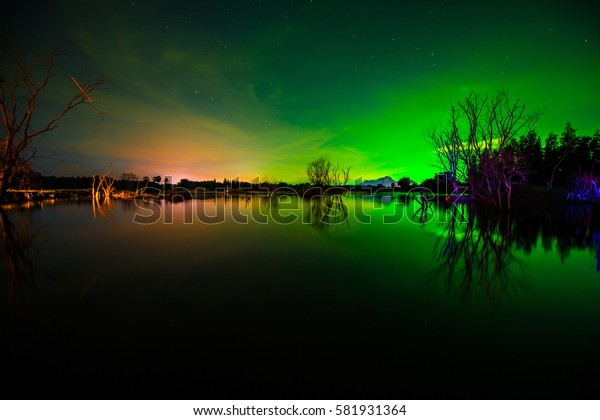 Dark night sky beautiful green  ,  Northern lights above forest and mountain. Captured near Skibon