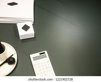 Dark office desk with white calculator, notes and other supplies