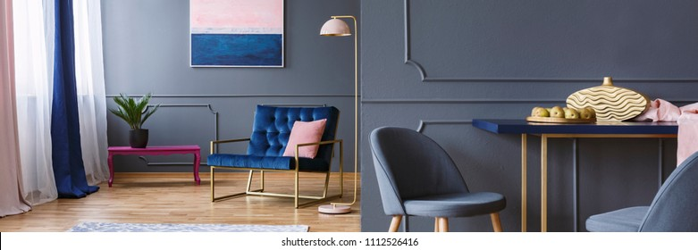 Dark open space living room interior with royal blue armchair, fresh plant, apples on dining table and painting on wall with molding