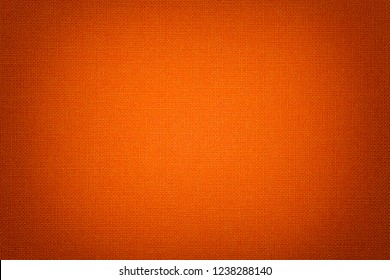 Dark orange background from a textile material with wicker pattern, closeup. Structure of the bright red fabric with texture. Cloth backdrop with vignette.