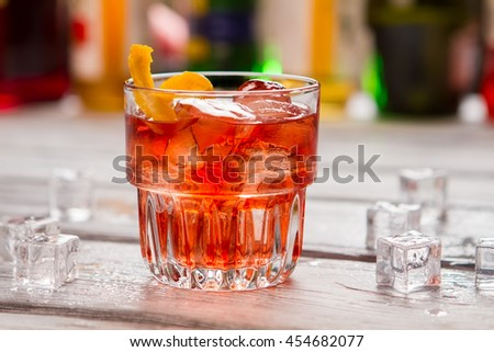 Dark orange drink in glass. Ice cubes and lemon peel. Negroni served at local bar. Vermouth and gin.