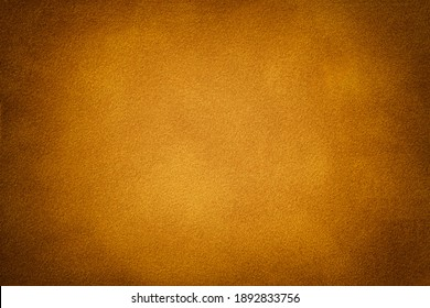 Dark orange matte background of suede fabric with vignette, closeup. Velvet texture of seamless golden textile with gradient, macro. Structure of amber felt canvas backdrop.
