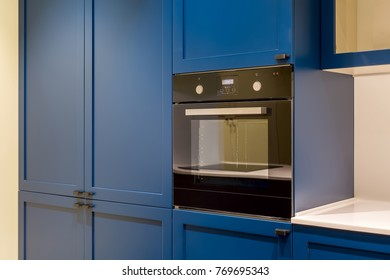 Dark oven which built-in in the blue kitchen with lockers and a white tabletop. Closeup. Horizontal.