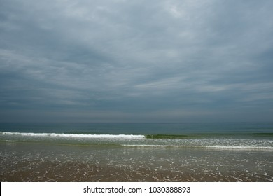 Dark and overcast seascape with sky filling two thirds of the frame. The stark white foamy of breaking waves partially bisects the page. Ocean water is deep green blue. Sand fills in the foreground.