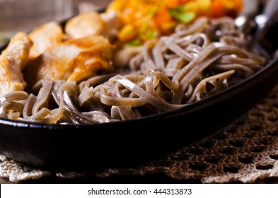 Dark pasta with steamed vegetables and grilled chicken. Selective focus.