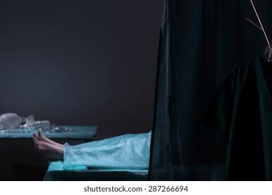 Dark photo of dead body lying in morgue