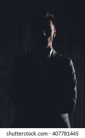 Dark photo of serious man in suit posing with crossed hands