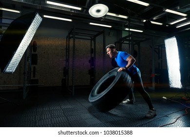 dark photo of a strong bodybuilder with a heavy wheel in the gym