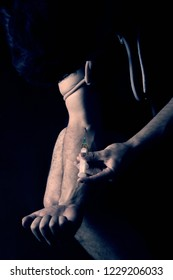 A dark photo of a young man who injects the drug into a vein.Detail of the arm of a junkie who injects a drug into a vein.