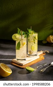 Dark photography of a cold drink, a glass of mojito with mint leaf, ice, lemon and sugar on a wooden table with a vintage style.
