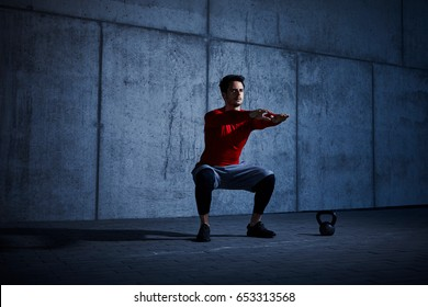 Dark picture of athlete doing squats
