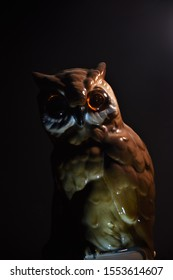 Dark picture with an owl sculpture, focus is on the head