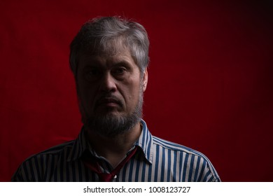 dark portrait of a bearded man on a red background