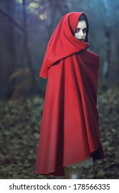 Dark portrait of a beautiful woman with red cloak posing in the woods. Fantasy and magic