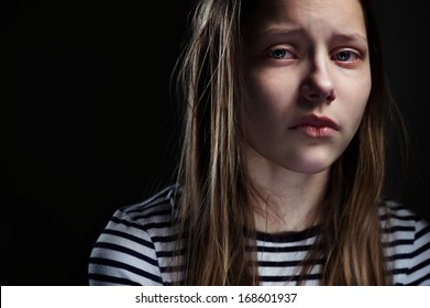 Dark portrait of a crying teen girl, studio shot