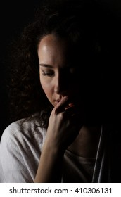 Dark portrait of curly womanl isolated on dark background