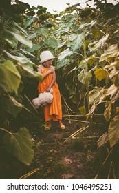Dark portrait of cute girl in sunflowers field
