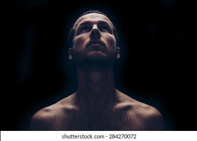 dark portrait of an handsome man looking up