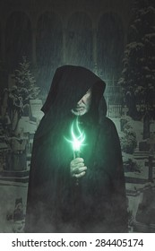 Dark portrait of hooded wizard with graveyard background . Fantasy and halloween