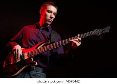 Dark portrait of musician with bass guitar