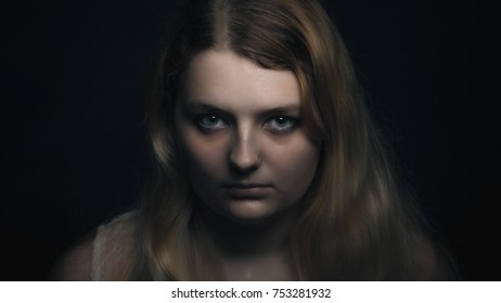 Dark portrait of a young blonde woman in a white dress