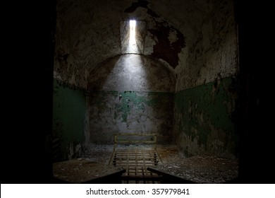 Dark prison cell with collapsing dirty walls in the Eastern State Penitentiary abandoned ruins decay