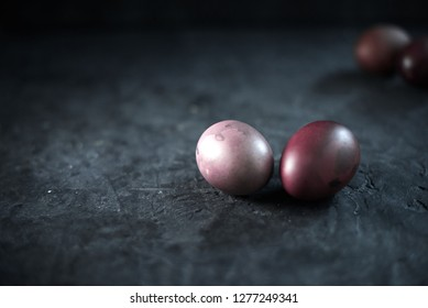 Dark purple eggs on a rough cement background.