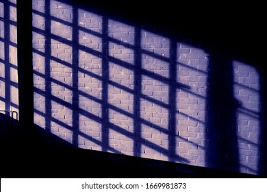 Dark quadratic shadow on a stonework wall illuminated by blood red light - concept dramatic contrast film noir mystic interior texture background surface structure window horror pattern detail evening
