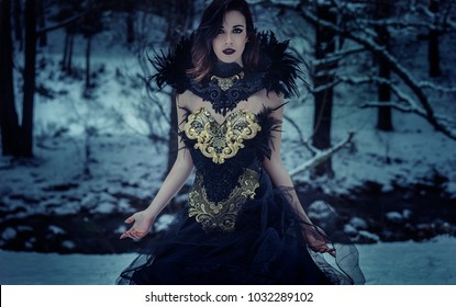Dark queen, Beautiful brunette woman with gothic dress made in gold and black threads. It is in a snowy forest in winter. fantasy concept