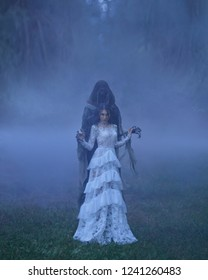 dark Queen with neat hairdo in a white vintage dress and a silver necklace, standing in a forest full of thick purple fog. A powerful witch summoned the power of darkness. Devil's bride. Art photo
