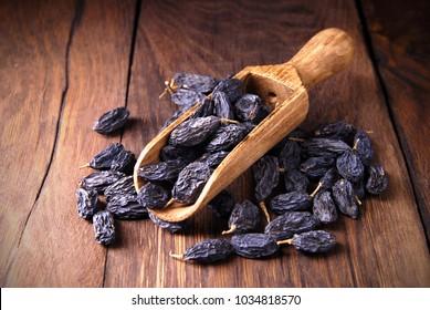 Dark raisins in a scoop on a dark wooden background.