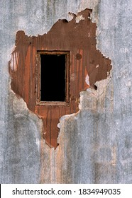 Dark rectangular window on old peeling paint wooden door