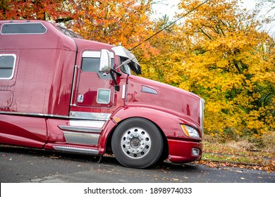 Dark Red American Idol classic big rig semi truck tractor with chrome accessories and vertical exhaust pipes and dry van semi trailer standing on the sloping city street parking with autumn trees
