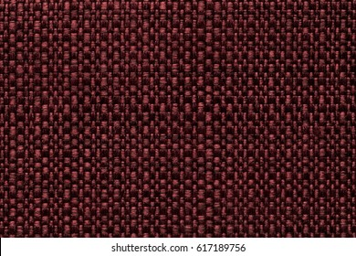 Dark red background with checkered pattern, closeup. Structure of the wine fabric macro.