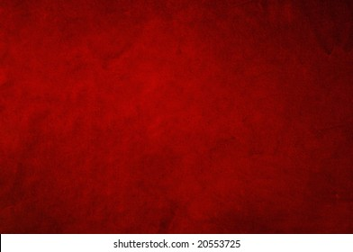 Dark red background fabric with soft folds and smudges in uneven candlelight.