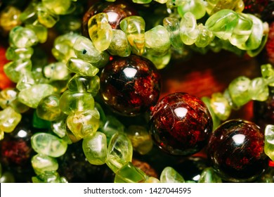 Dark red beads of garnet and olive green peridot gravel, natural stone close up.