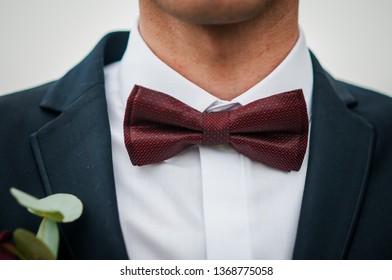 Dark red bowtie on the grooms neck