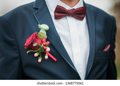 Dark red bowtie on grooms neck and red rose on the jacket