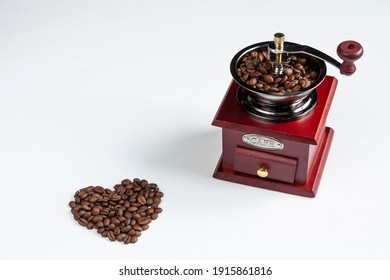 a dark red coffee grinder and coffee beans forming a heart on white background